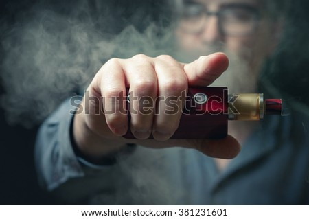 Man shrouded in e-cigarette vapor, pointing back at the viewer. - stock photo