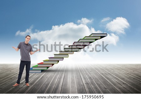 Man shrugging his shoulders against book steps against sky - stock photo