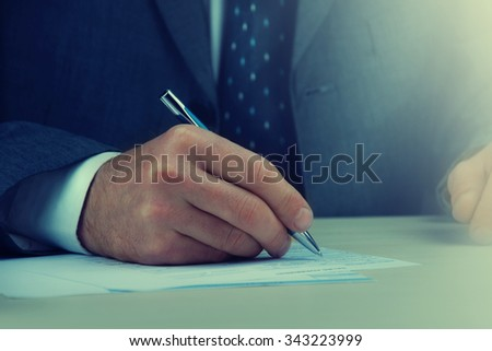 Man signing a document or writing correspondence with a close up view of his hand with the pen. - stock photo