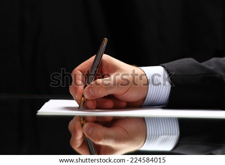 Man signing a document or writing correspondence with a close up view of his hand with the pen and sheet of notepaper on a desk top  - stock photo