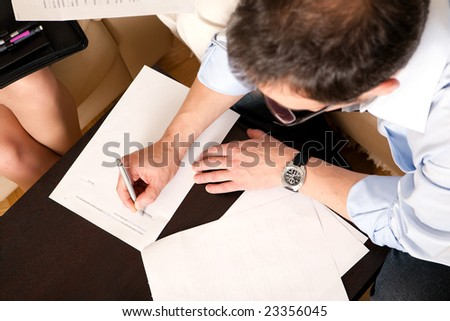 Man signing an agreement.  Just sign here - stock photo