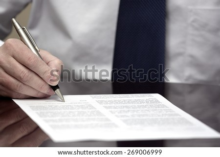 Man signing contract or agreement paper with pen wearing white shirt and tie - stock photo
