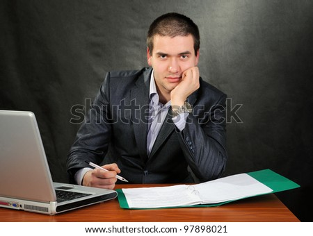 Man signs documents. On a dark background. - stock photo