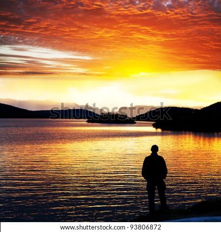 man silhouette at sunset lake, Norway - stock photo