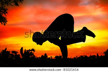 Man silhouette doing bakasana, crane pose with tree nearby outdoors at sunset background - stock photo