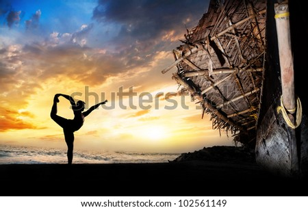 man silhouette doing natarajasana dancer pose on the beach near the fisherman boat at sunset background in Varkala, Kerala, India - stock photo