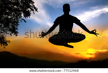 Man silhouette doing padmasana lotus pose in jumping with tree nearby outdoors at sunset background - stock photo