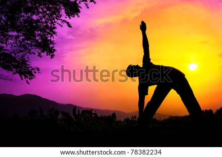 Man silhouette doing utthita trikonasana triangle pose with tree nearby outdoors at sunset background