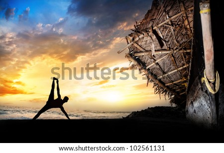 man silhouette doing vasisthasana side plank pose on the beach near the fisherman boat at sunset background in Varkala, Kerala, India - stock photo