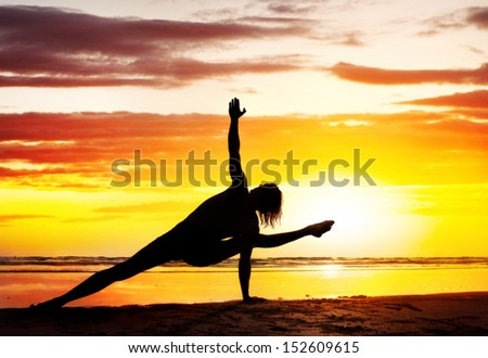 Man silhouette doing Yoga on the beach near the ocean in India - stock photo