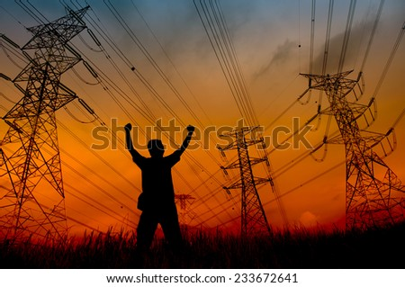 Man silhouette in the sunset sky with hand rise up at the high-voltage tower  - stock photo