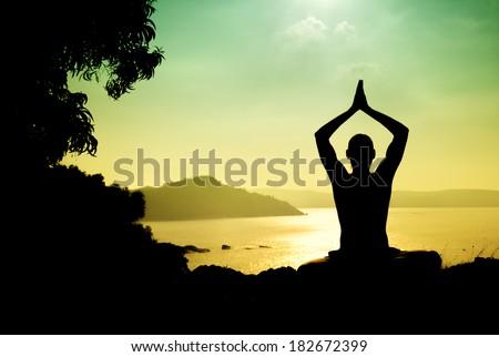 Man silhouette in Yoga meditation pose near the ocean in Gokarna, Karnataka, India - stock photo
