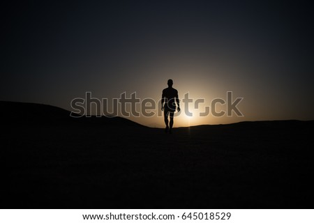 man silhouette. silhouette of walking man on sunset fiery sky background in mountain, sport and recreation, future and success, people and nature, speed and healthy lifestyle