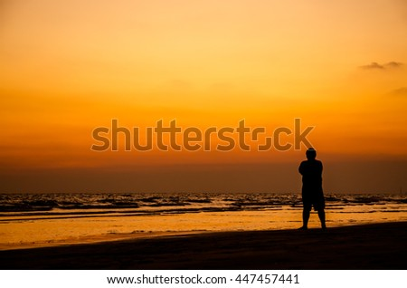 Man silhouette stand alone on the beach