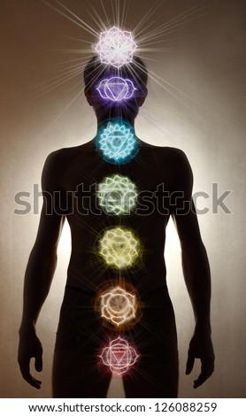 Man silhouette standing, chakra symbols - stock photo