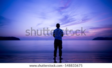 Man silhouette, standing on the beach and contemplating a beautiful sunset.