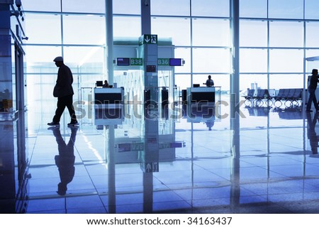 Man silhouette walking in a modern airport - stock photo
