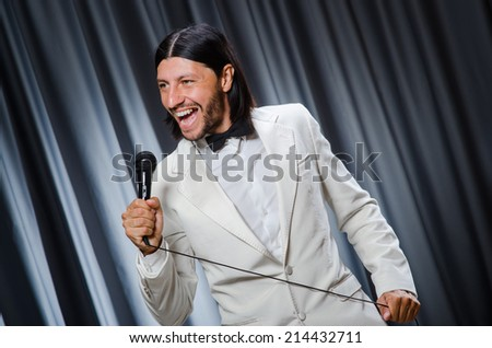 Man singing in front of curtain in karaoke concept - stock photo