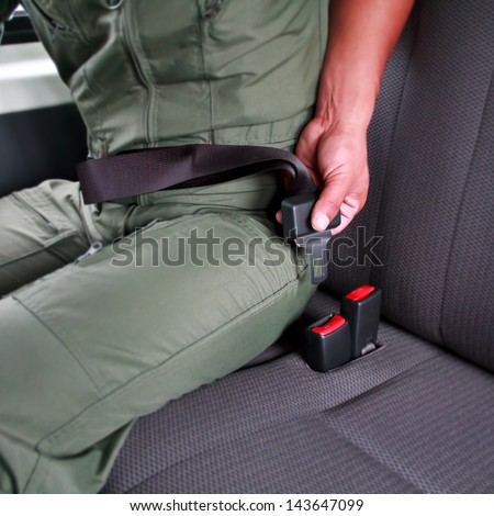 man sit on car seat and fasten safety belt - stock photo