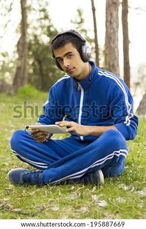 Man sit with tablet on the grass in the park and listening music - stock photo