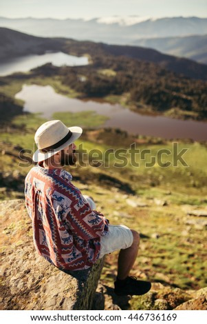 Man sited in a rock looking at the lake in the mountains