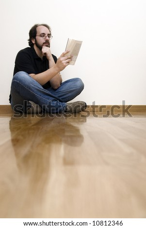 Man siting on a wooden floor reading a book