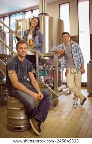 Man siting on keg and his colleague holding a glass of beer in the factory - stock photo