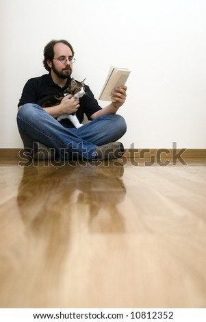 man siting on the floor with his cat while reading a book