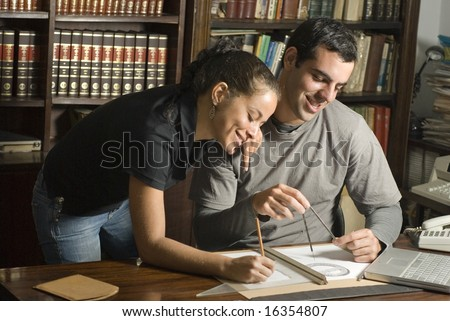 Man sits and woman leans next to him over table. There are maps and tools on the table and they are smiling. Horizontally framed photo. - stock photo