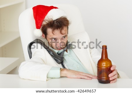 Man sits at a table and suffers from a hang-over - stock photo