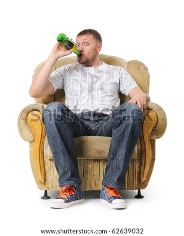 Man sits in an armchair and drinks beer on withe background - stock photo