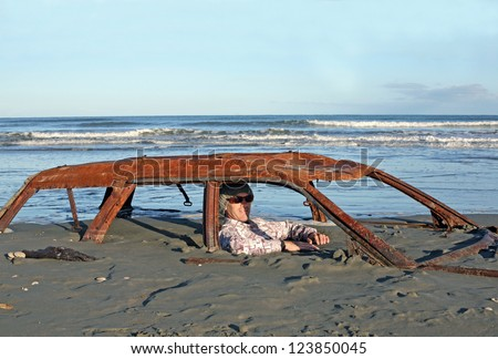 Man sits in rusted car wreck buried in sand on Waitarere Beach in New Zealand - stock photo