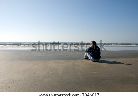 Man sits on a remote island shoreline alone thinking about life, family, love and work.
