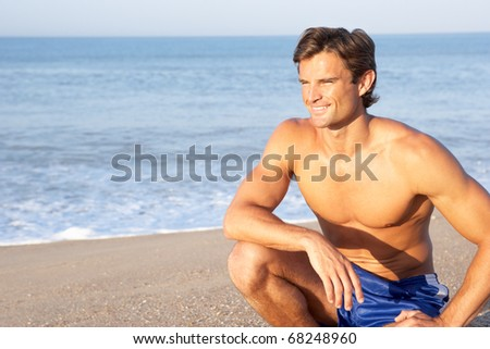 Man sits on beach relaxing - stock photo