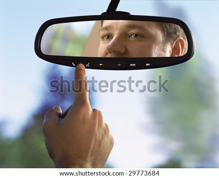 man sits on driver's seat and Looks in the rear-view mirror