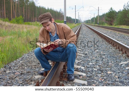 Man sits on railway and with enthusiasm reads book