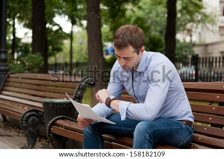 Man sits on the bench and read documents in the public garden