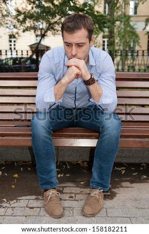 Man sits on the bench and relax in the public garden - stock photo