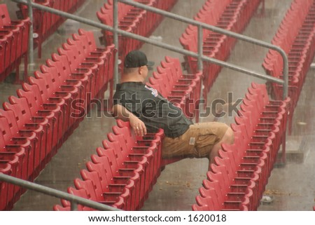 Man sits out rain delay - stock photo