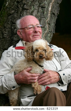 Man sitting against birch tree with a poodle