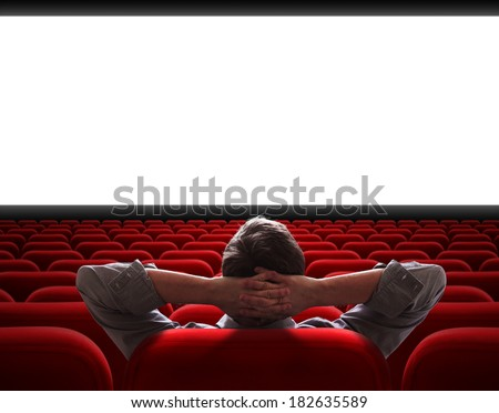 man sitting alone in empty cinema hall - stock photo