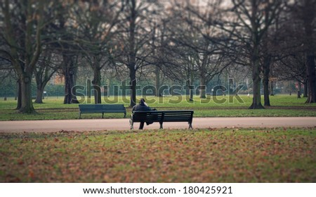 man sitting alone on a bench in the park in London - stock photo