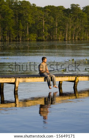 Man sitting alone on a dock fishing into a bay as the sun is setting. - stock photo
