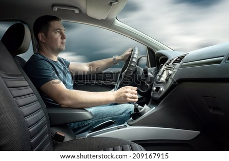 Man sitting and driving in the car - stock photo