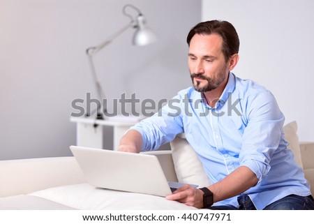 Man sitting and using laptop - stock photo