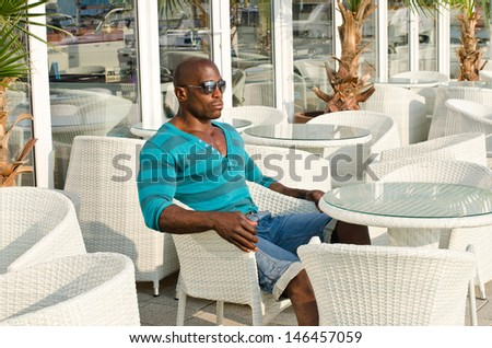 Man sitting at a bar. Handsome fit man sitting alone a street terrace. Summer  outdoors. - stock photo