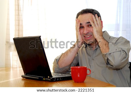Man sitting at a desk and looking into his computer - stock photo