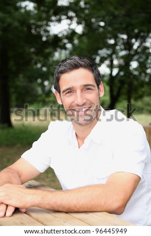 Man sitting at a table in a park