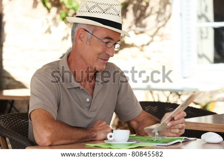 Man sitting at an outdoor cafe table - stock photo