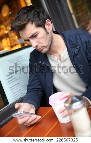 Man sitting at coffee shop, checking email on smartphone